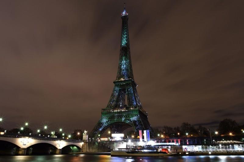 Menara Eiffel di Paris, Prancis, disorot sinar berwarna hijau untuk menyampaikan pesan perubahan iklim di hari pertama KTT COP21, Senin (30/11/2015). (Foto: AFP/STEPHANE DE SAKUTIN)