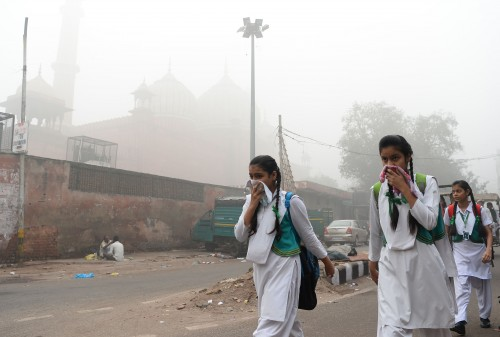 Indian schoolchildren cover their faces as they walk to school