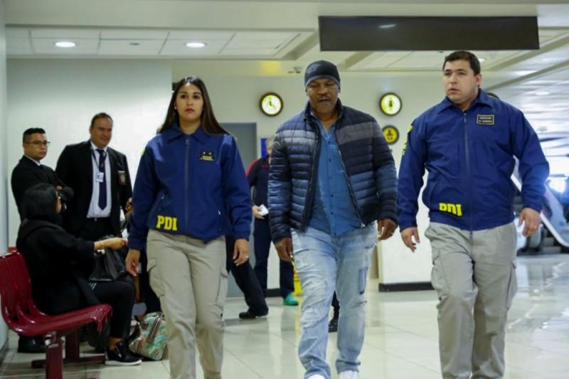 Mike Tyson sedang digelandang pihak keamanan Cile. (AFP CHILE'S INVESTIGATIONS POLICE)