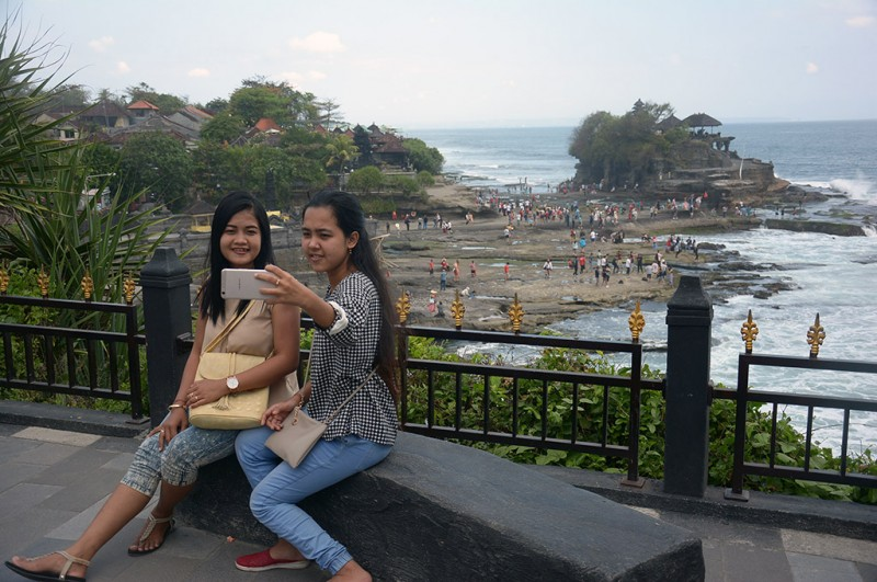 Wisatawan berfoto dengan latar Pura Tanah Lot, Tabanan, Bali -- ANT/Wira Suryantala
