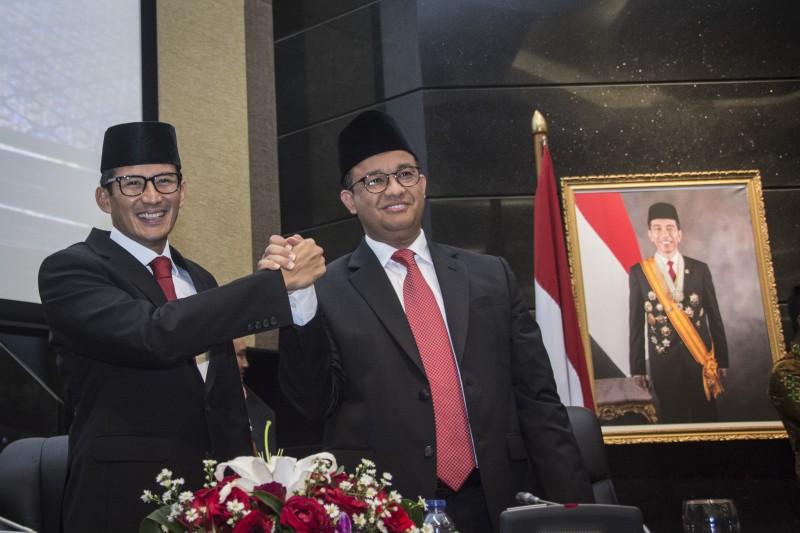 Gubernur DKI Jakarta Anies Baswedan (kanan) berjabat tangan dengan Wakil Gubernur Sandiaga Uno (kiri)--Antara/Aprillio Akbar