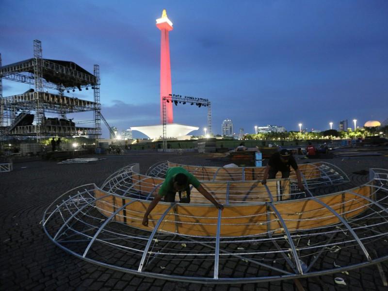 Pekerja menyelesaikan pembuatan panggung hiburan yang akan digunakan pada perayaan tahun baru di lapangan silang Monas, Jakarta, Kamis (28/12) - MI/Ramdani