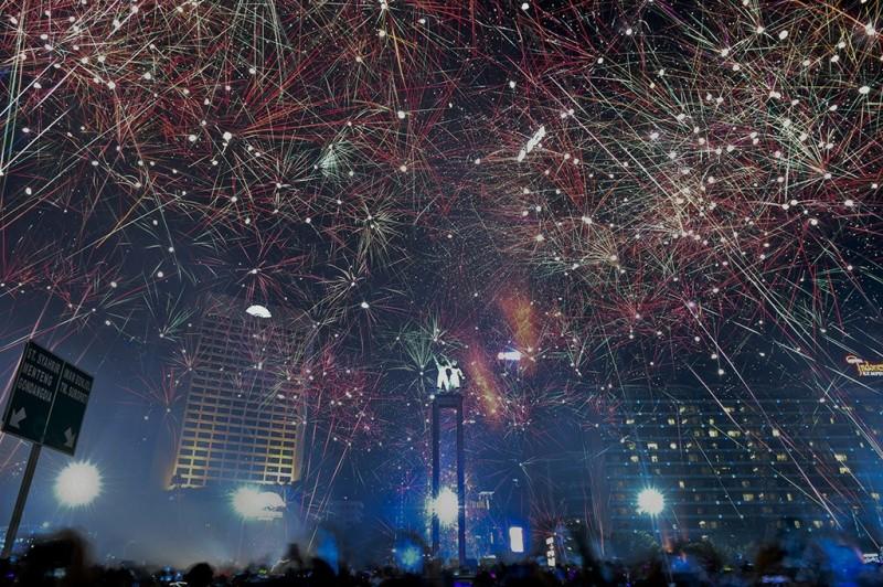 Suasana pesta kembang api saat malam tahun baru 2018 di kawasan Bundaran HI, Jakarta. Sejumlah warga ibukota dan sekitarnya memadati kawasan itu untuk merayakan malam pergantian tahun 2017 ke 2018. ANTARA FOTO/Hafidz Mubarak A