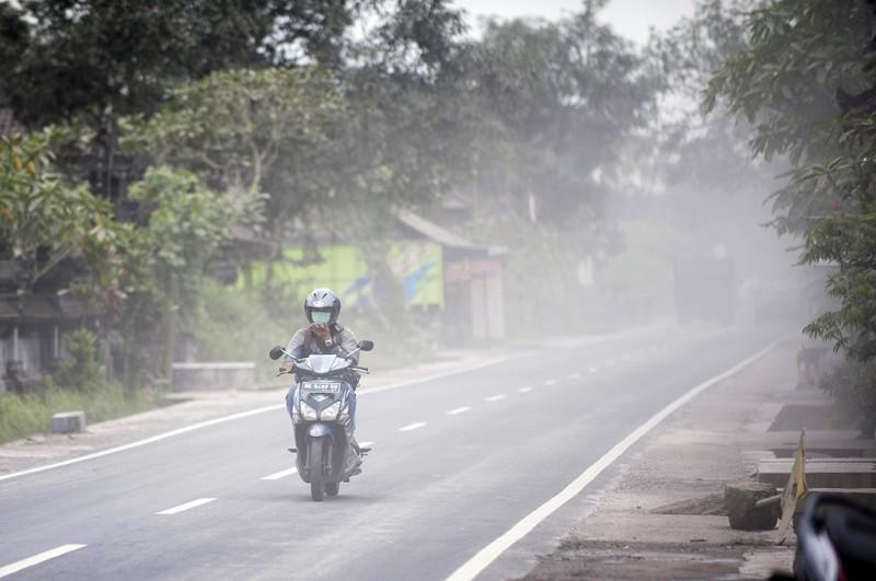 Pengendara melintas di jalan yang terkena abu vulkanis di Desa Rendang, Karangasem, Bali -- ANT/Nyoman Budhiana