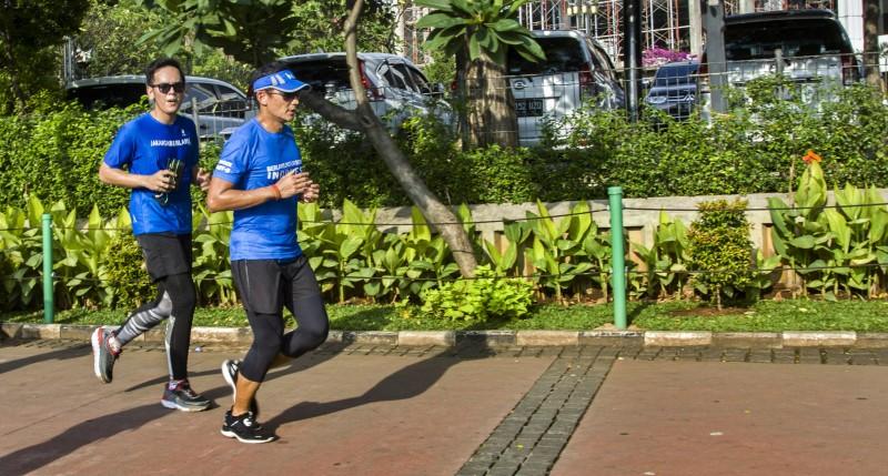 Wakil Gubernur DKI Jakarta Sandiaga Uno (kanan) berlari menuju Balai Kota, di Jakarta, Jumat (20/10)/Foto: Antara/Galih Pradipta