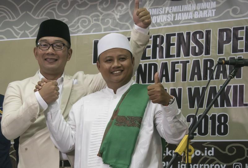 Bakal calon Gubernur Jawa Barat Ridwan Kamil (tengah) dan bakal calon Wakil Gubernur Jawa Barat Uu Ruzhanul Ulum (kanan) berpose usai pendaftaran. Foto: Antara/Novrian Arbi