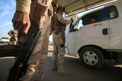 An Iraqi soldier searching for weapons and wanted people