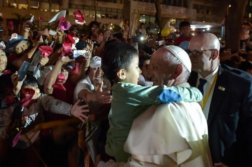 Paus Fransiskus memeluk seorang bocah dalam kunjungannya ke