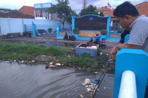 Warga membersihkan sampah dari sungai di Sidoarjo, Selasa 23