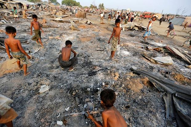 Anak-anak di sebuah desa di Rakhine mengais puing-puing dari rumah-rumah yang dibakar saat operasi militer Myanmar beberapa bulan lalu. Foto/REUTERS/Soe Zeya Tun