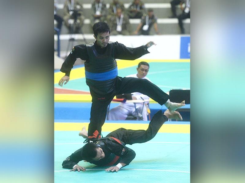 Pesilat Abdul Malik (biru) saat mengalahkan pesilat Malaysia M Faizul Nasir (merah)-(INASGOC)