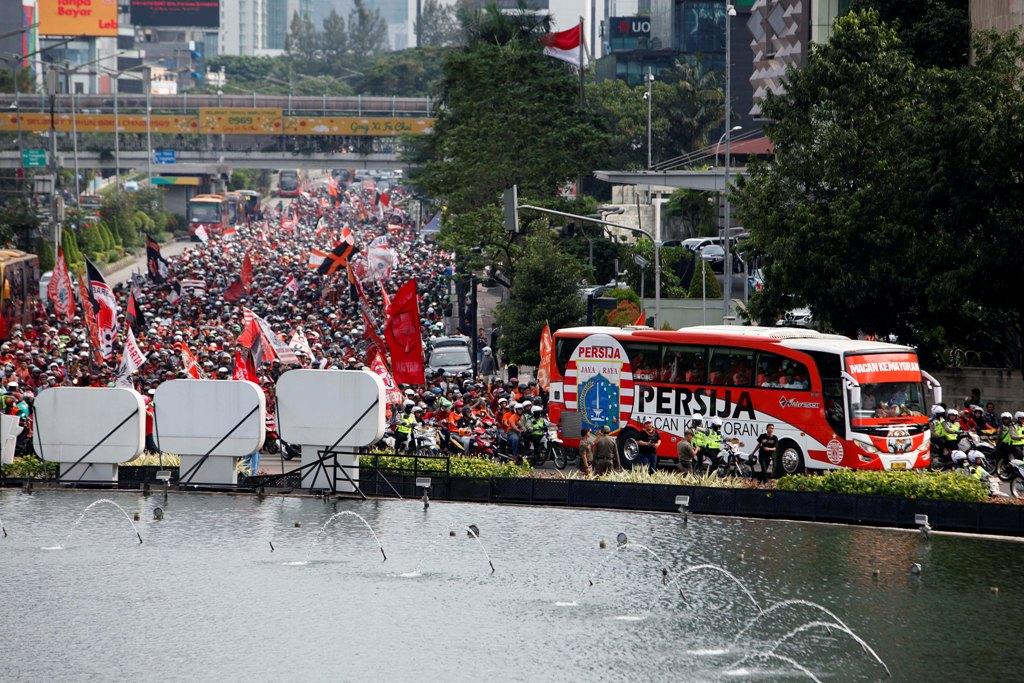 Ribuan The Jakmania (suporter Persija) mengiringi bus yang membawa para pemain dan ofisialPersija Jakarta ketika pawai dalam rangka keberhasilan meraih Piala Presiden 2018 saat melintas di Bundaran HI, Jakarta Pusat, Minggu (18/2). (MI/ROMMY PUJIANTO)