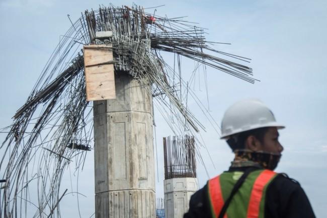 Pekerja beraktivitas di dekat tiang pancang yang roboh pada proyek kontruksi pembangunan Tol Becakayu di Jalan DI Panjaitan, Jakarta, Selasa (20/2/2018). Foto: Antara/Aprillio Akbar.