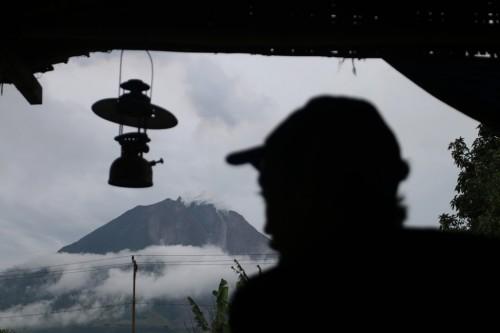Warga beraktivitas dengan latar belakang Gunung Sinabung, di