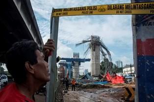Warga mengamati tim Labfor Bareskrim Pori melakukan olah tempat kejadian perkara (TKP) pasca robohnya tiang pancang pada proyek kontruksi pembangunan tol Bekasi-Cawang-Kampung Melayu (Becakayu) di Jalan D I Panjaitan, Jakarta. (Foto: ANTARA/Aprillio Akbar