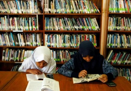 ILUSTRASI: Dua siswa membaca buku di Perpustakaan Daerah Kota