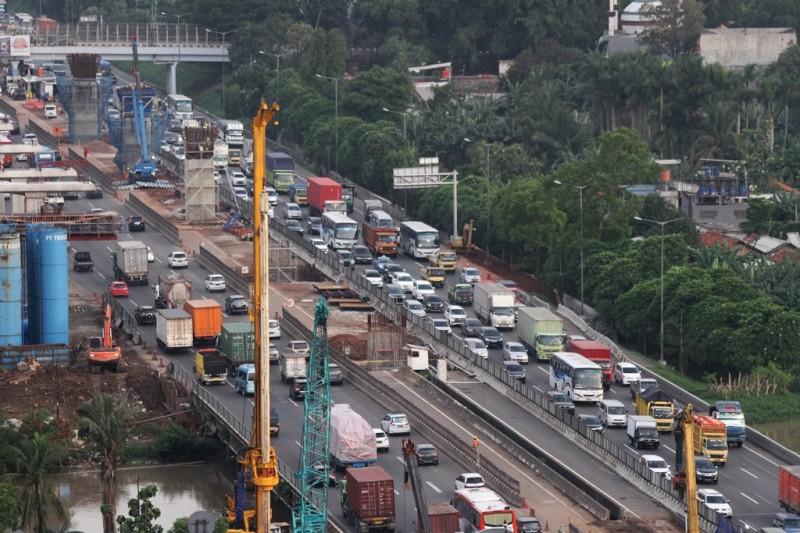 Kendaraan melintas di samping salah satu lokasi pengerjaan pembangunan infrastruktur di ruas Jalan Tol Jakarta-Cikampek. (ANTARA FOTO/Risky Andrianto)