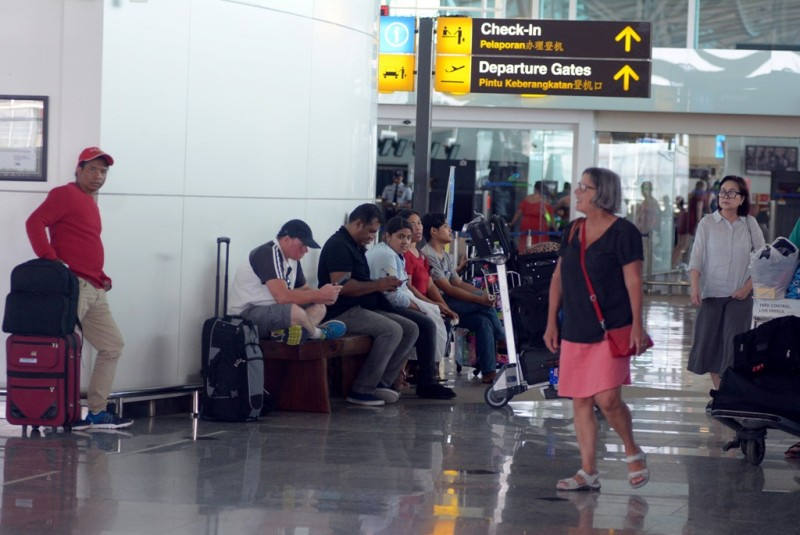 Sejumlah penumpang menunggu jadwal keberangkatan pesawat di terminal internasional Bandara Ngurah Rai, Bali. (FOTO: ANTARA FOTO/Wira Suryantala)