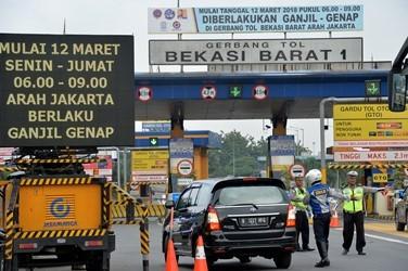 Sejumlah Polisi dan Dishub mengarahkan kendaraan roda empat berplat nomor ganjil berputar balik keluar dari gerbang tol Bekasi Barat 1 di Bekasi, Jawa Barat. (ANT/Widodo S Jusuf)