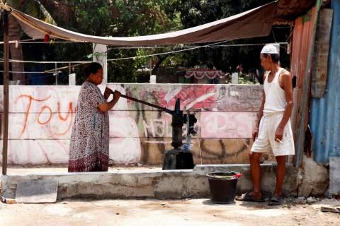 Warga mengambil air bersih dengan alat pompa air tradisional di