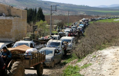 Syrian civilians ride their cars through Ain Dara in Syria's