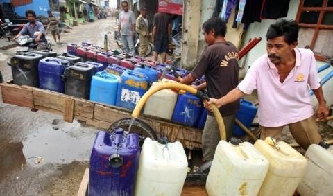 Ilustrasi. Penjual air keliling mengisi air bersih kedalam