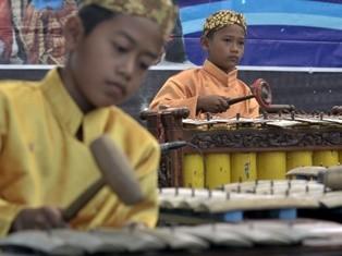 Sejumlah pelajar sekolah dasar memainkan alat musik gamelan saat