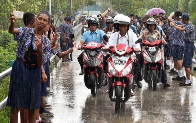 Serombongan siswa SMP menyambut Presiden Jokowi dan Ny. Iriana yang berboncengan sepeda motor dalam kondisi hujan saat berkeliling Agats. Antara Foto/Puspa Perwitasari