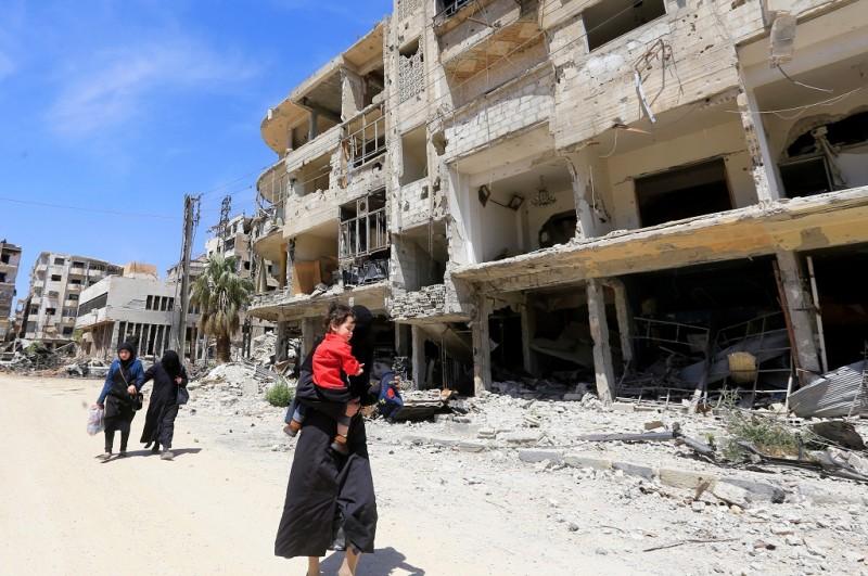 Warga Suriah berjalan melewati bangunan yang rusak di kota Douma, Ghouta Timur, 16 April 2018. (Foto: AFP/LOUAI BESHARA)