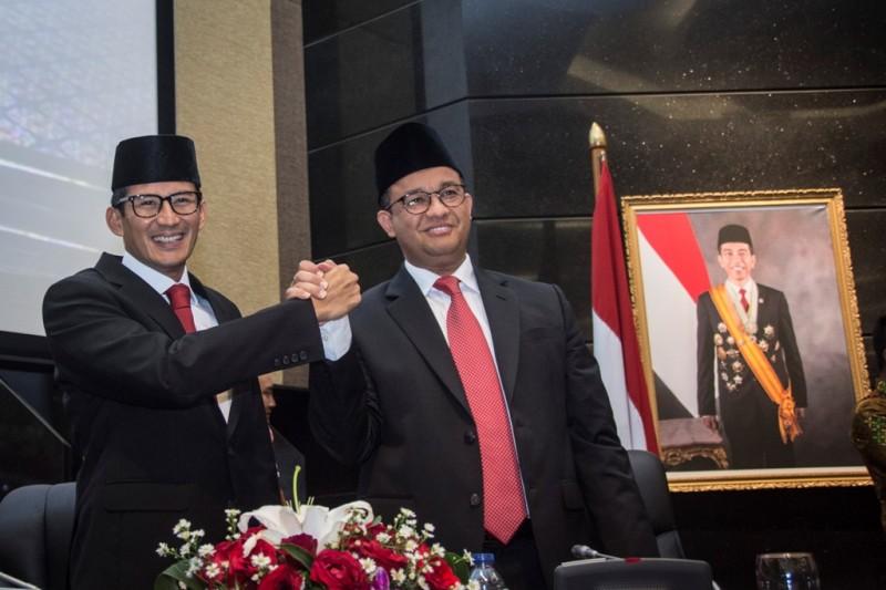 Gubernur DKI Jakarta Anies Baswedan (kanan) berjabat tangan dengan Wakil Gubernur Sandiaga Uno (kiri) seusai rapat paripurna di DPRD DKI Jakarta. Foto: Antara/Aprillio Akbar.