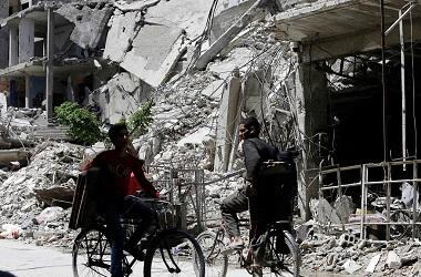 Warga Suriah bersepeda di kota Douma, Ghouta Timur, 16 April