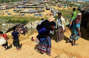 Seorang pengungsi Rohingya menggendong ibunya yang kurang sehat