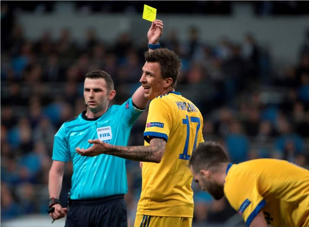 Wasit Michael Oliver memberikan kartu kuning kepada Mario Mandzukic. (Foto: AFP PHOTO / Curto DE LA TORRE)