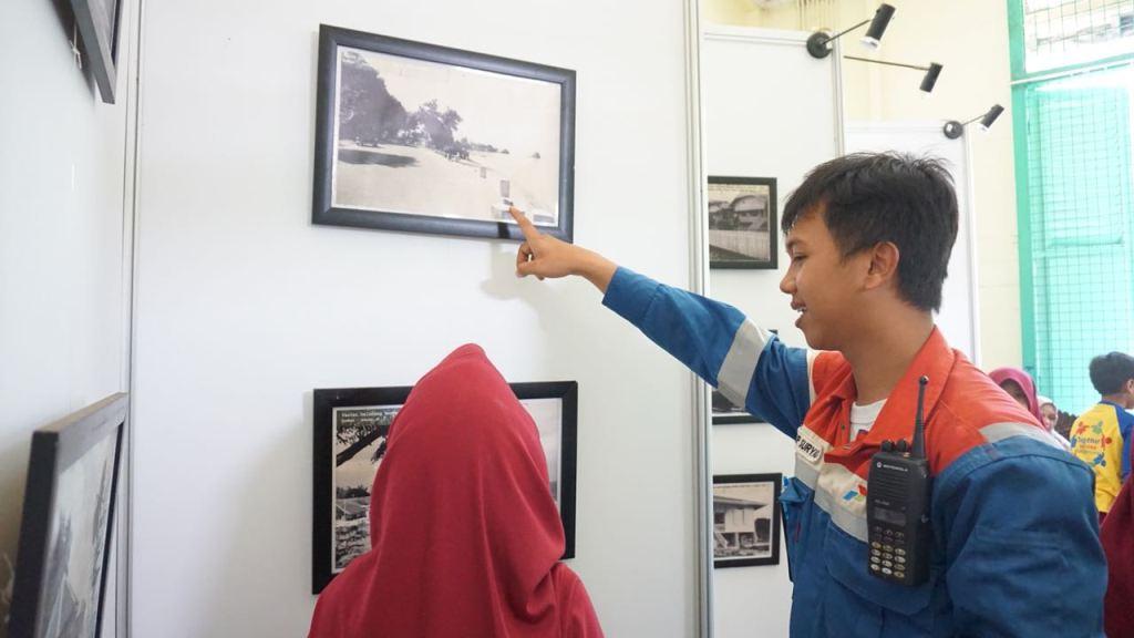 Pekerja Pertamina menjelaskan kepada pengunjung foto-foto sejarah di Rumah Cagar Budaya Dahor. (FOTO: dokumentasi Pertamina)