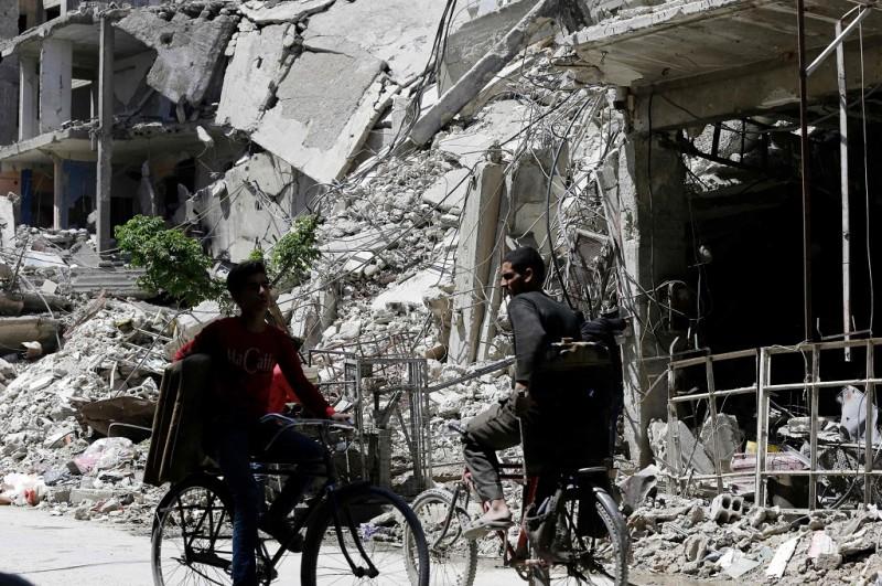 Warga Suriah bersepeda di kota Douma, Ghouta Timur, 16 April 2018. (Foto: AFP/LOUAI BESHARA)