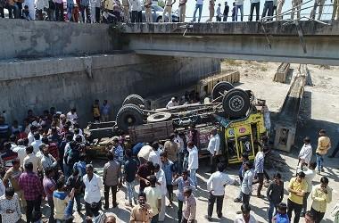 Warga melihat sebuah truk yang jatuh dari jembatan di distrik