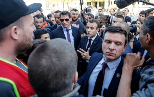 Surrounded by bodyguards, French President Emmanuel Macron