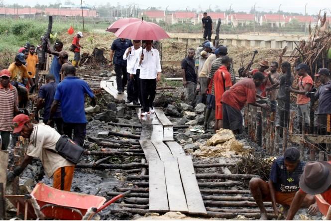 Presiden Joko Widodo (kanan) didampingi Menteri Pekerjaan Umum dan Perumahan Rakyat (PUPR) Basuki Hadimuljono (kiri) mengunjungi pembangunan jalan program padat karya tunai di Kampung Kokoda, Distrik Sorong Manoi, Sorong, Papua Barat Jumat (13/4). Antara