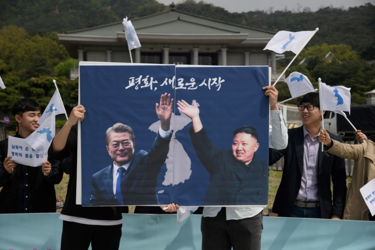 Activists hold a peace placard showing the leaders of North and South Korea at a rally in Seoul. (Photo:AFP/Ed Jones)