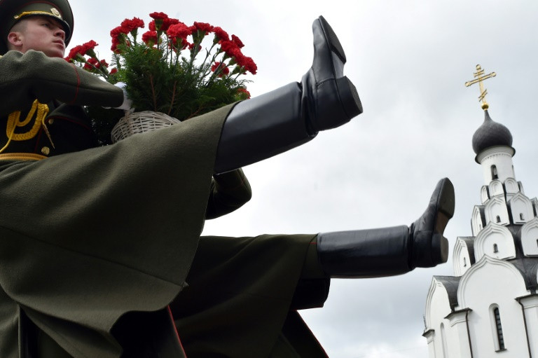Soldiers bearing flowers at the Chernobyl victims' memorial in Minsk. (Photo:AFP/Sergei Gapon)