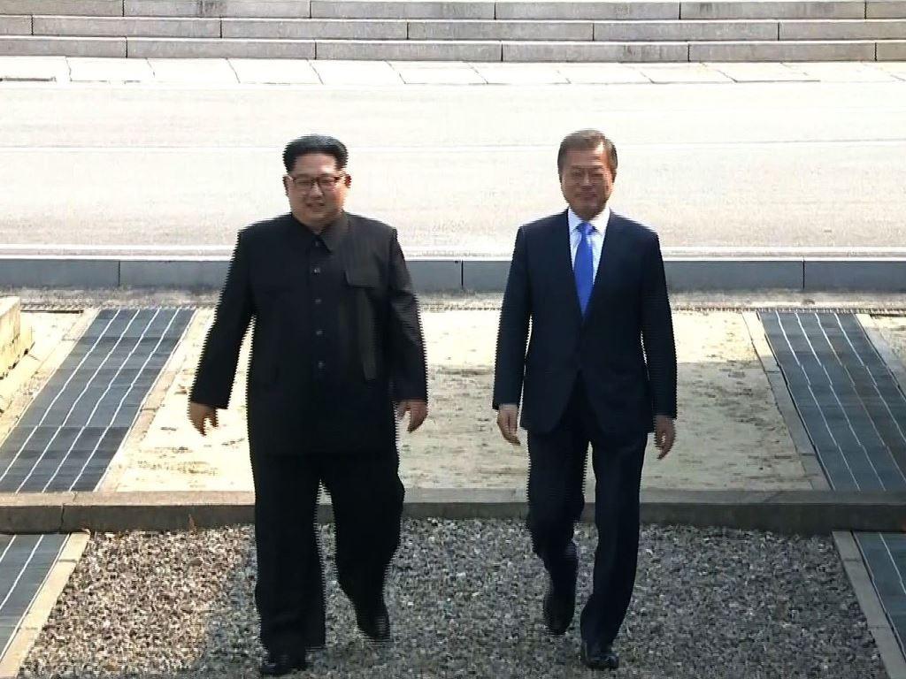 Pemimpin Korut Kim Jong-un (kiri) berjalan bersama Presiden Korsel Moon Jae-in ke Gedung Perdamaian. (Foto: AFP).