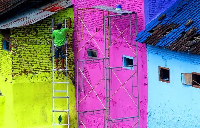 Seorang pemuda mengecat dinding dan atap rumahnya di bantaran Sungai Brantas, Jodipan, Malang, Jawa Timur. Kampung ini dicat warna-warni untuk menghilangkan kesan kumuh sekaligus menjadikannya sebagai obyek wisata alternatif. Antara Foto/Ari Bowo Sucipto