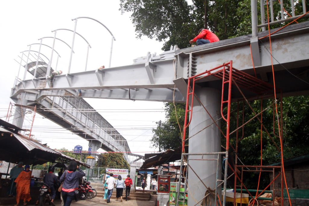 Pekerja menyelesaikan pembangunan jembatan penyeberangan orang (JPO) di Stasiun Lenteng Agung, Jakarta. Foto: MI/Bary Fathahilah.