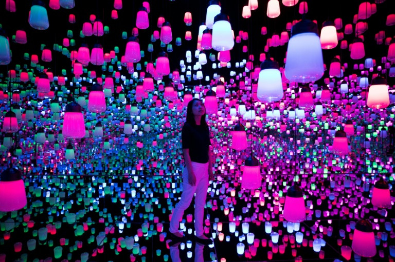 A member of the teamLab collective walks through a digital installation room in Tokyo featuring hanging lamps that light up as the visitor nears. (Photo:AFP/Behrouz Mehri)