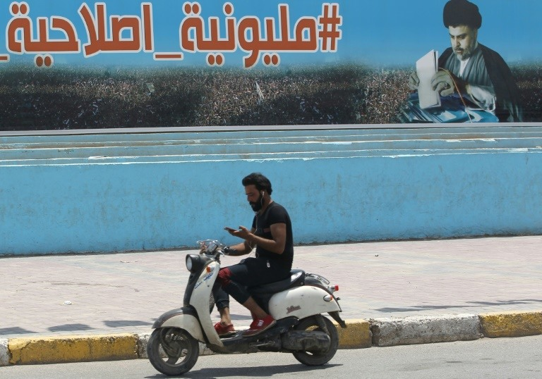 A man rides his scooter past a poster of Shiite cleric Moqtada Sadr in Sadr City, east of the Iraqi capital, on May 14, 2018. (Photo:AFP/Ahmad Al-Rubaye)
