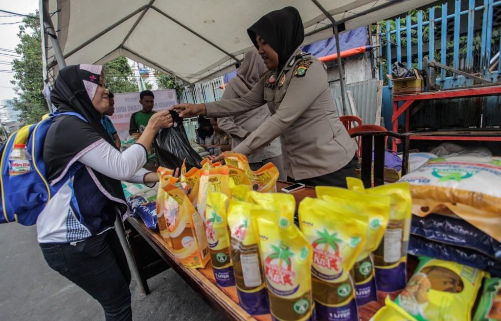 Warga membeli bahan pokok pada ajang pasar murah Polda Metro Jaya, di kawasan Pasar Karang Anyar, Jakarta. Foto: Antara/Makna Zaezar.
