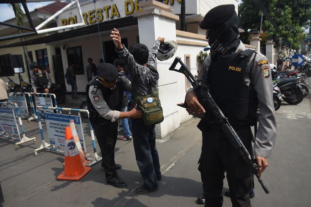 Polisi memeriksa badan dan barang bawaan pengunjung yang akan memasuki kantor Polresta Depok, Jawa Barat. (Foto: ANTARA/Indrianto Eko Suwarso)