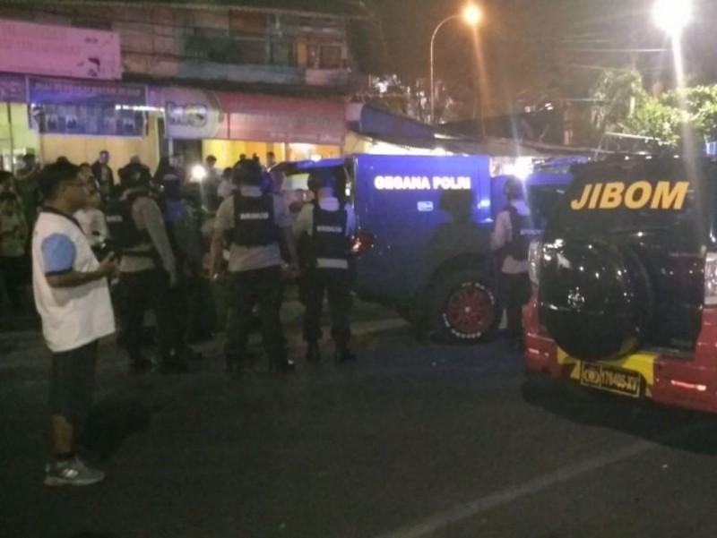 Polisi berjaga di area penemuan koper hitam misterius di Jalan Piere Tendean, Manado. (Foto: Medcom.id/Mulyadi Pontororing).