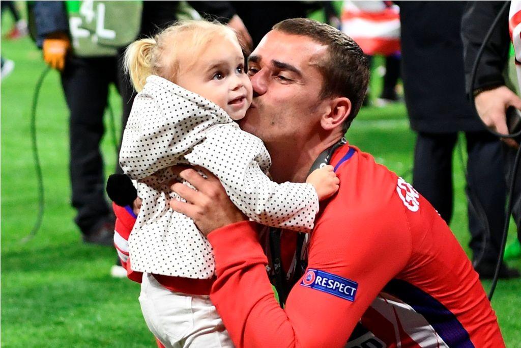 Antoine Griezmann mencium anaknya usai meraih Liga Europa. (Foto: AFP PHOTO / FRANCK FIFE)