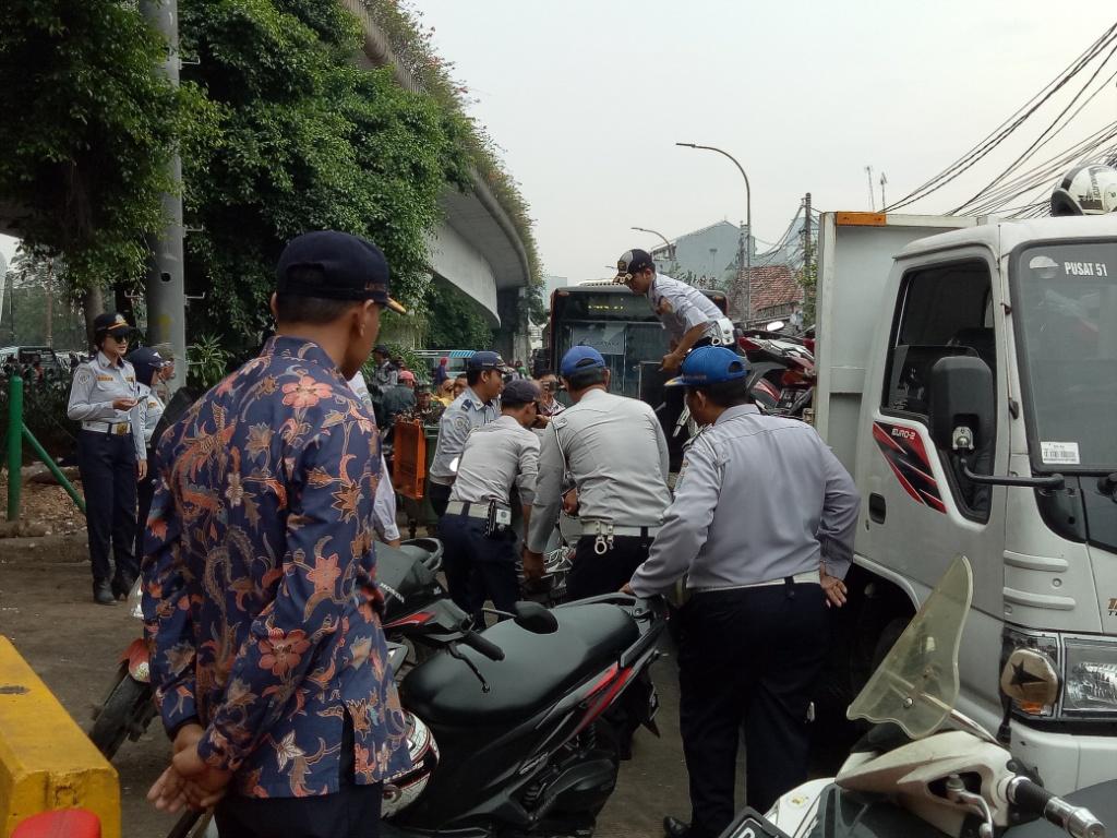 Petugas Dishub mengangkut motor personel Satpol PP yang parkir sembarangan. Foto: Medcom.id/Siti Yona Hukmana.